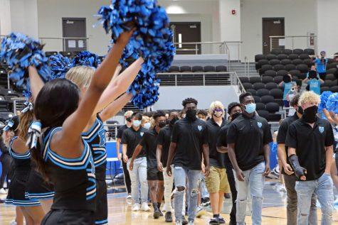 "Cheerleaders wave as the football team walks down the arena court. Football played their first game last Thursday against Frisco Heritage but lost. ""We haven"