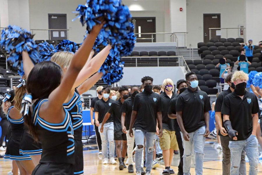 Cheerleaders wave as the football team walks down the arena court. Football played their first game last Thursday against Frisco Heritage but lost.