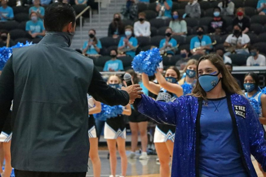 Theatre teacher and pep rally host Sariea Haney hands the microphone off to football coach Mark Humble. Administration had to make a last minute change of who could attend the rally due to positive COVID-19 cases. The upcoming Friday Oct. 2 football game has been canceled due to additional cases.