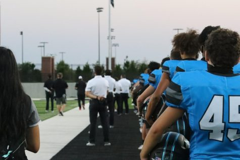Football players listen to the national anthem at the first home game of the season. Football had to cancel a couple games for COVID-19 concerns. The Forthcoming football game will be played at Children