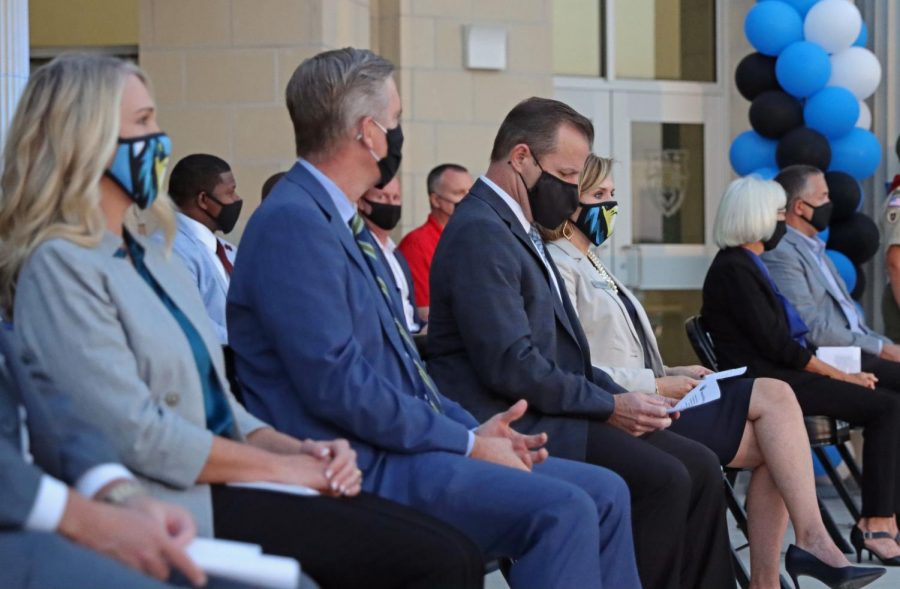 Former superintendent Drew Watkins sits with new superintendent Holly Ferguson. Assistant principals Dedrick Buckels, Melissa Weiss and other members of administration made appearances at the ceremony. The school offered cookies, waters and commemorative coins at the outside event.