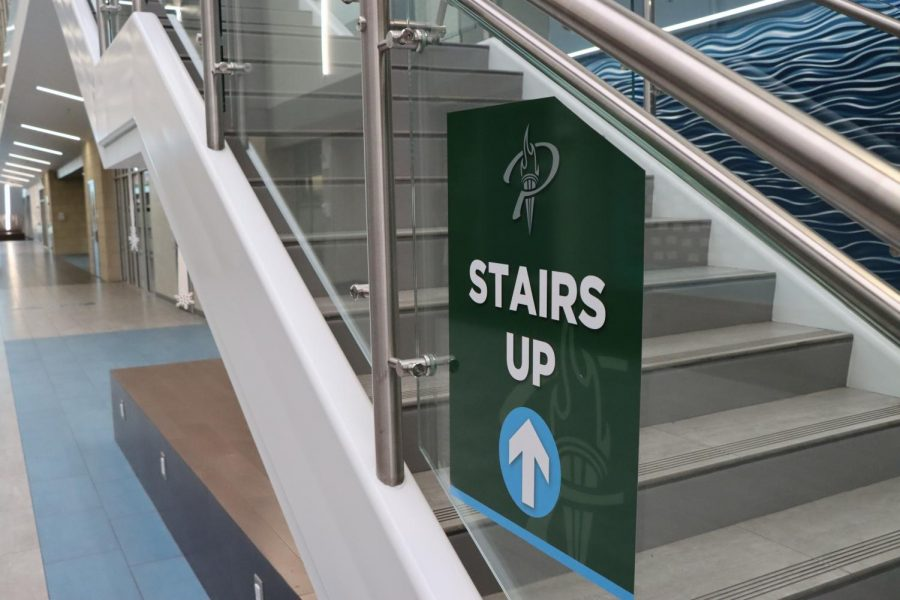A sign depicting which way students should use the staircase hangs in the hallway. The school used these signs this year to help students navigate the halls with COVID-19 guidelines.