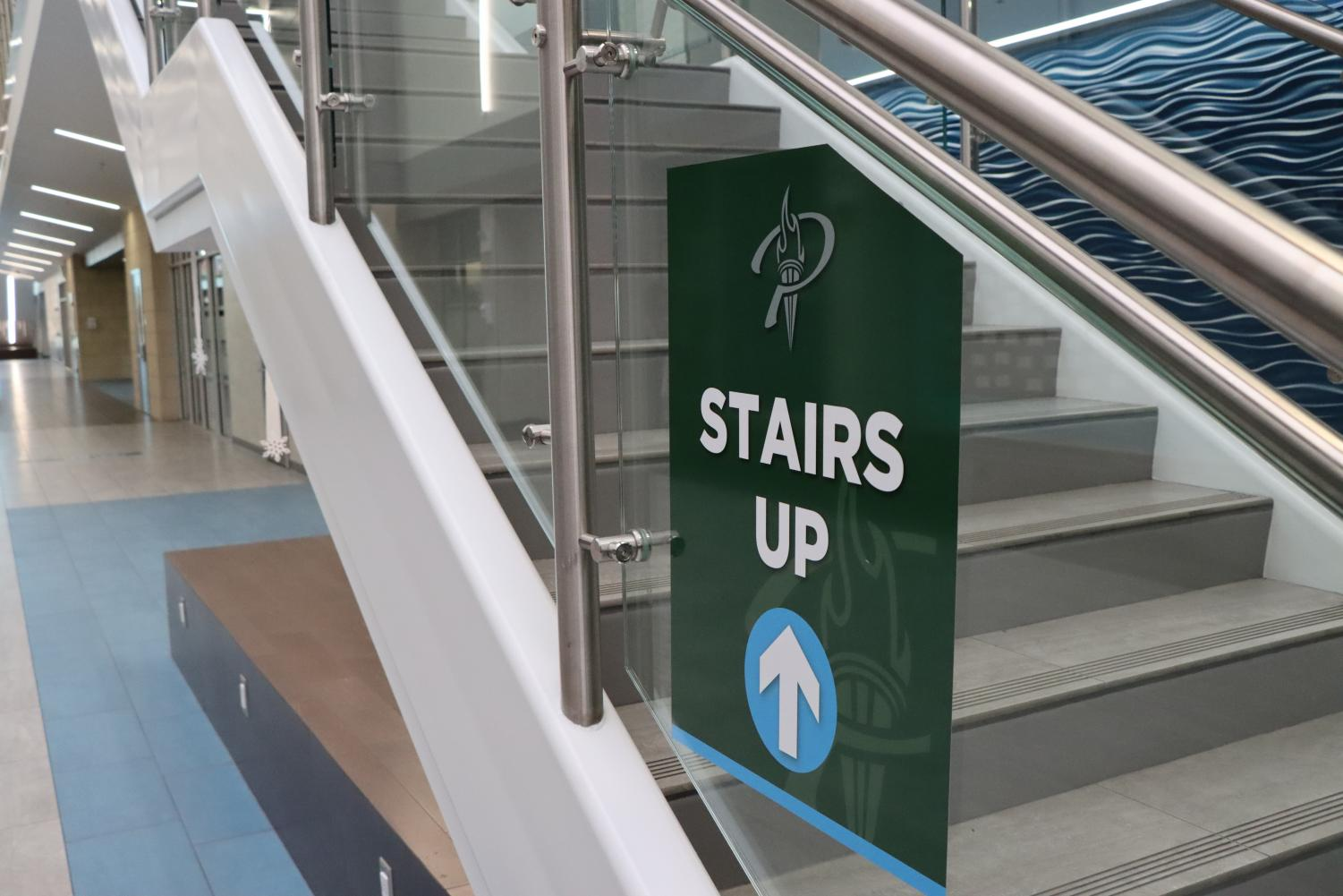 """A sign depicting which way students should use the staircase hangs in the hallway. The school used these signs this year to help students navigate the halls with COVID-19 guidelines. """"Listen to those who are smarter than us, and experts in the area,"""" science teacher Andy Bradstreet said. """"(Listen) to the opinions of immunologists, people in the CDC, things like that."""""""