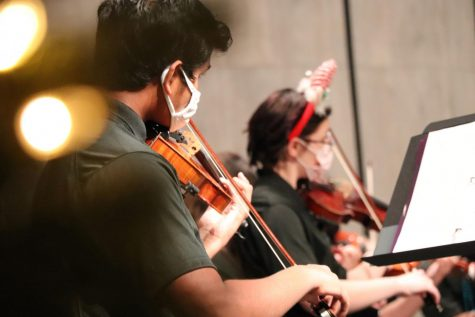 Violin players Prasanna Padmanathan and Hailey Percil Duncan perform at the orchestra concert Dec. 10. The group played holiday songs for family and students. The orchestra was able to play indoors while sporting masks and holiday gear.