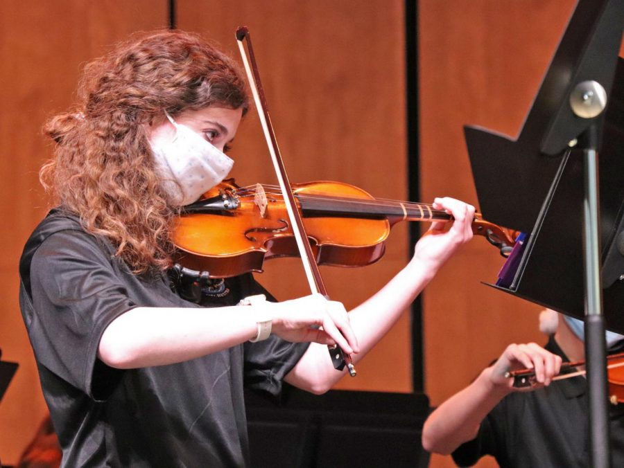 Violinist Gracie Clark plays at orchestra's holiday concert. Orchestra students performed in the new auditorium. Masks and COVID-19 precautions were used to ensure safety of all students and audience members.