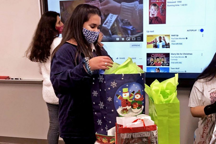 "Spanish Honor Society member Xiomara Sanchez looks at the ""white elephant exchange"" gifts in Spanish teacher Elizabeth Dzvonick"
