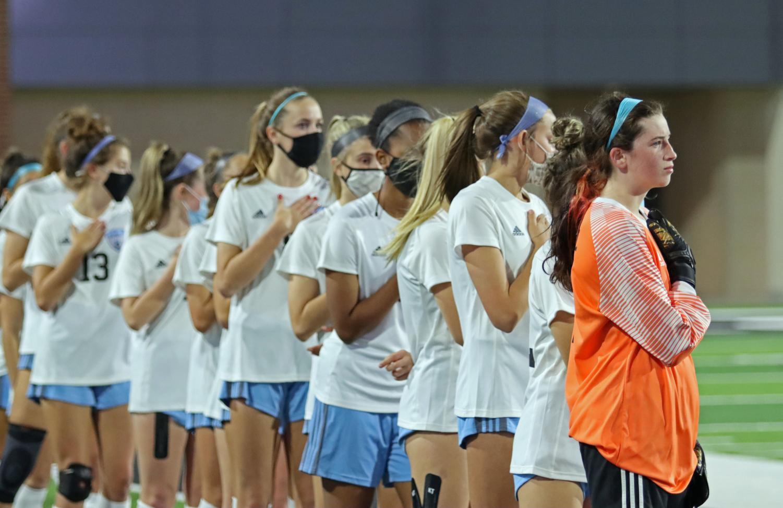 Varsity girls soccer stands on the sidelines at Children