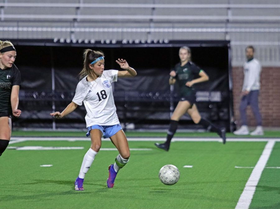 Sophomore forward Noemi Mistretta runs for the ball while surrounded by Prosper players. Although the team lost 0-2, this was Rock Hill athletics first game against a Prosper team. Parents and fans gathered in the stadium with masks and COVID-19 precautions.