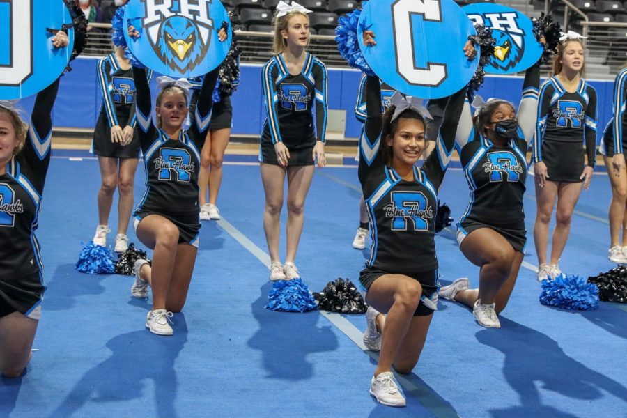 Cheer holds up signs at the spring Meet the Blue Hawks event. Other clubs such as color guard and the Rockettes performed, as well. The event took place in the high school arena and introduced spring athletics.