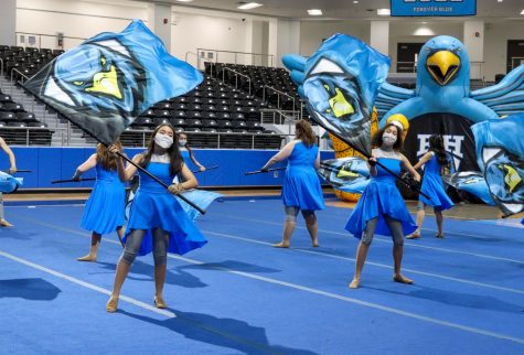 Color guard spins their flags at the Meet the Blue Hawks spring athletics event. The event featured performances by cheer and the Rockettes.