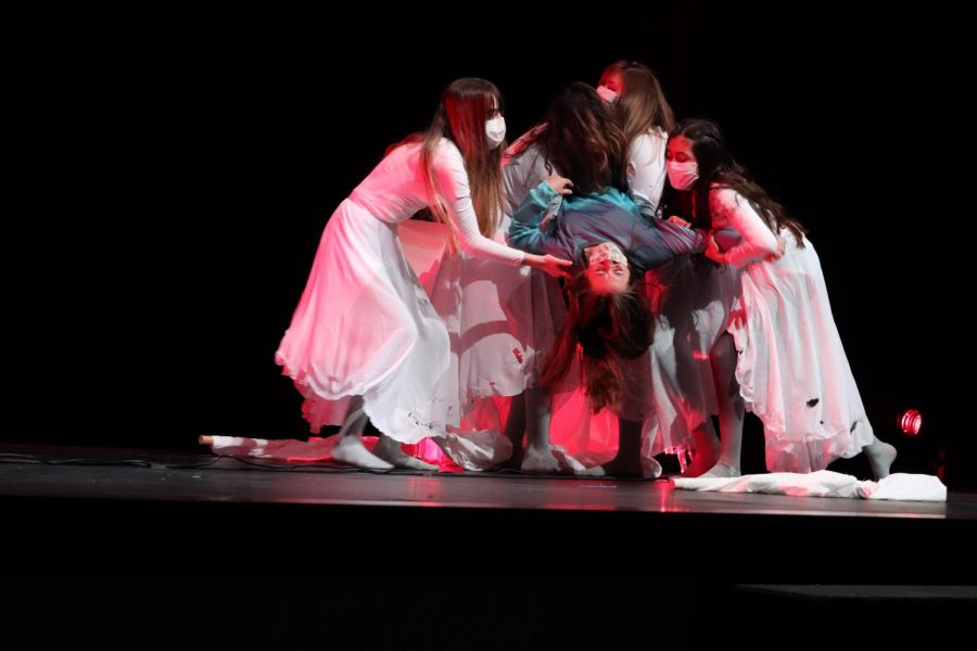 Sophomore Madelyn Goodwin, junior Ella Dellenbach, senior Kaitlyn Cyranowicz, and sophomore Margret Gardizi carry freshman Sasha Sims towards center stage during her death. I got so close to so many people and bonded over such an amazing show, Gardizi said. I think that I have grown with my strengths as an actress from watching some of the amazing people in our cast and learning new techniques for acting from our directors.